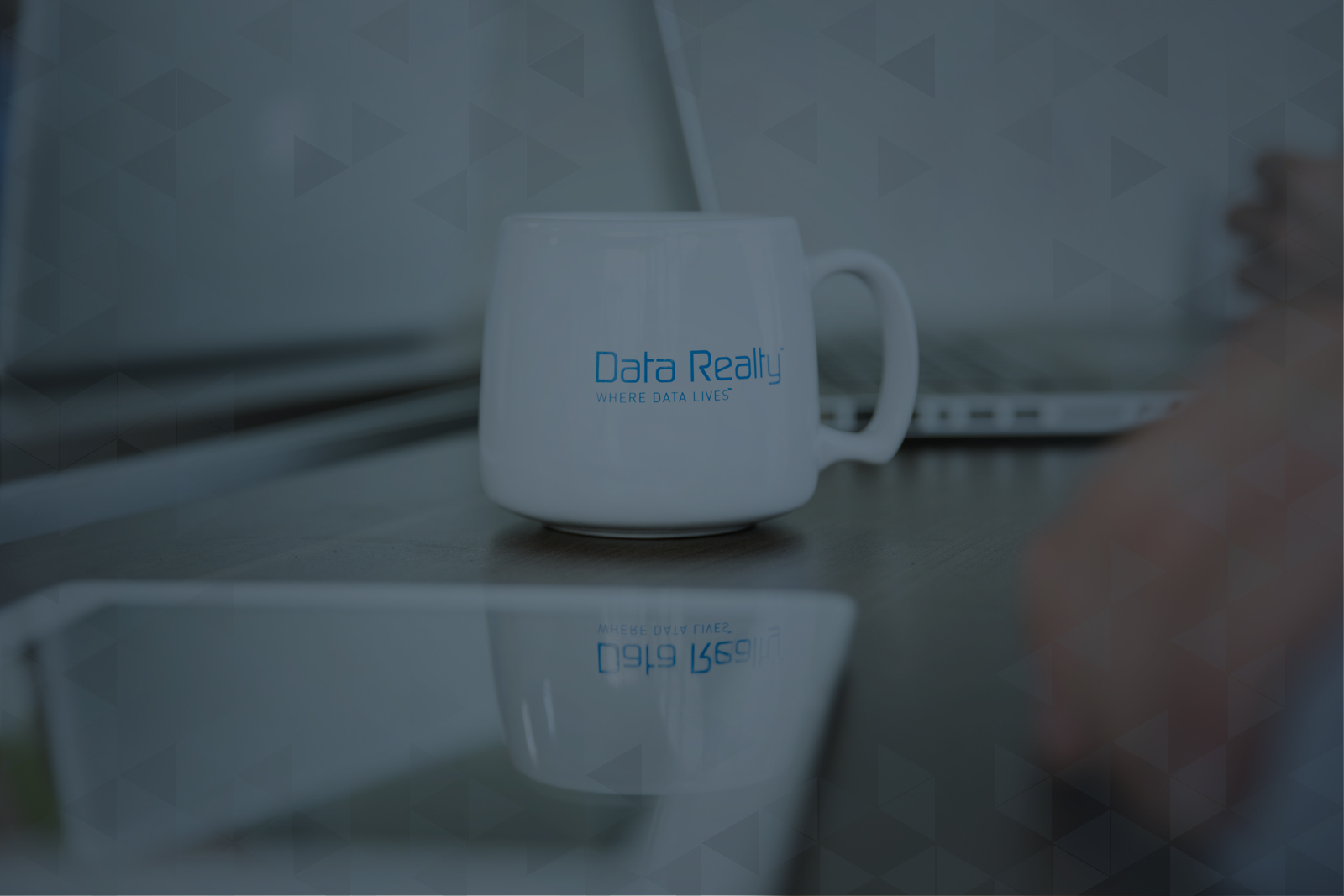 Data Realty mug surrounded by computer and tablet